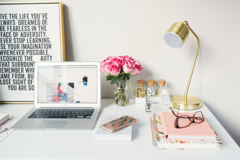 clean desk with a laptop, flowers, a gold lamp, and a pink spiral notebook